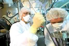 Two laboratory workers in full protective gear including hair covers, facemasks and sterile gloves.