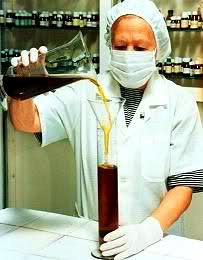 Woman in laboratory pouring liquid from one glass containter into another.